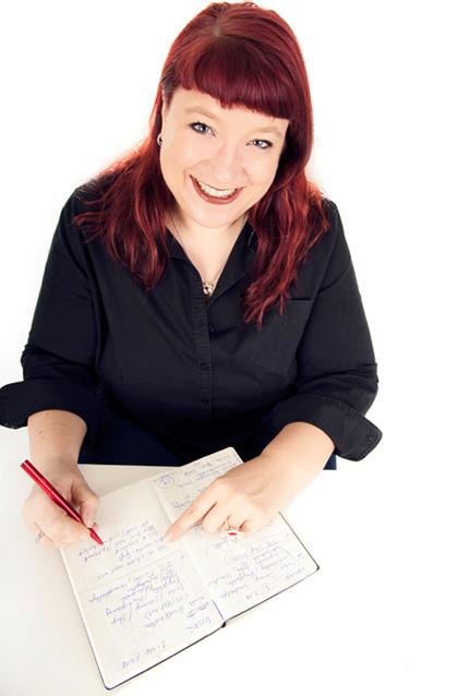 Christa Goede lächelt und schreibt in ein Notizbuch
