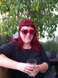 Christa sitzt auf dem Balkon und trinkt Apfelwein